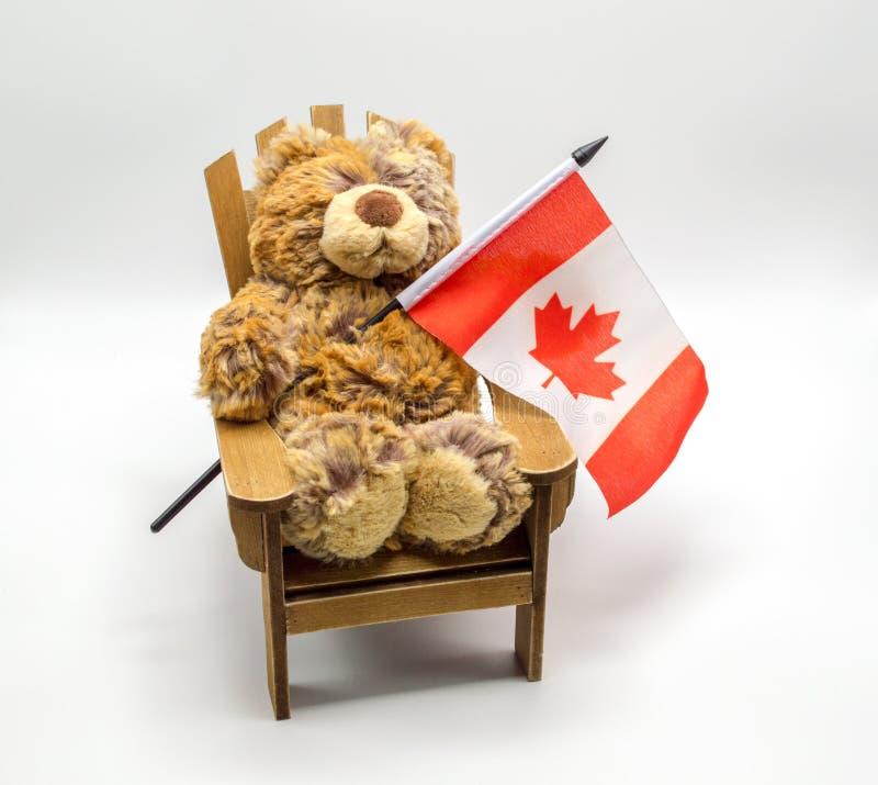 Ours de jouet de peluche dans une chaise jugeant un drapeau canadien de feuille d'érable d'isolement sur le blanc images stock