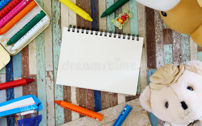 Ours de nounours avec le carnet et le crayon ouverts de blanc sur le fond en bois photos stock