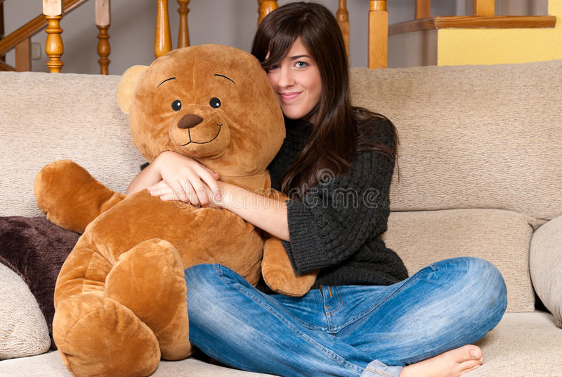 Ours de nounours d'embrassement de jeune femme se reposant sur le sofa photo stock