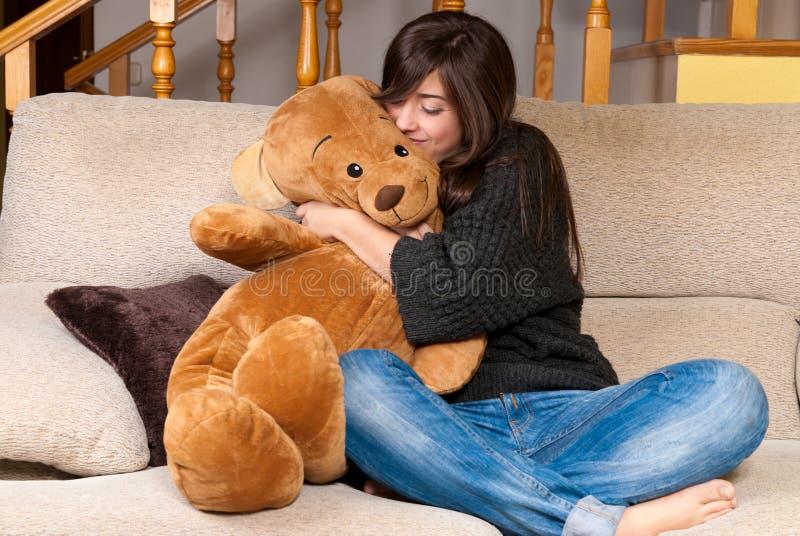 Ours de nounours d'embrassement de jeune femme se reposant sur le sofa photographie stock