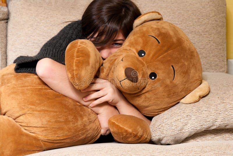 Ours de nounours d'embrassement de jeune femme se trouvant en fonction sur le sofa photographie stock