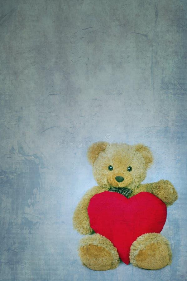 Ours de nounours de Brown avec le coeur mou sur le fond texturisé photographie stock libre de droits
