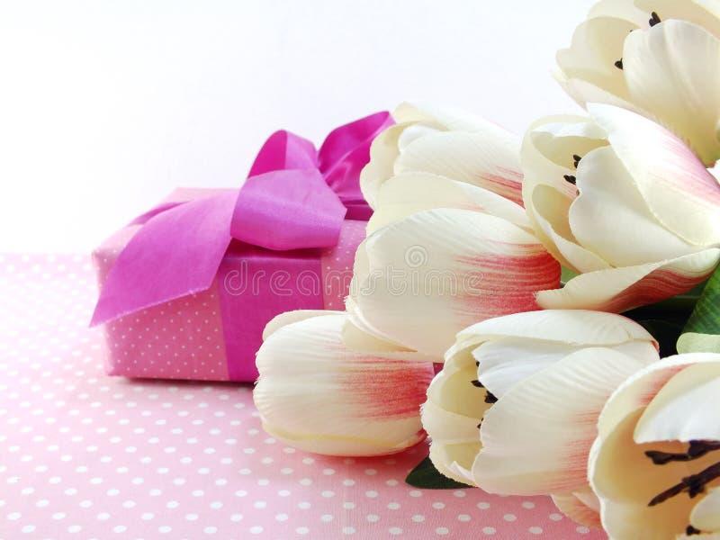 Ours de nounours rouge avec le fond de bouquet de fleurs artificielles de tulipe photographie stock libre de droits