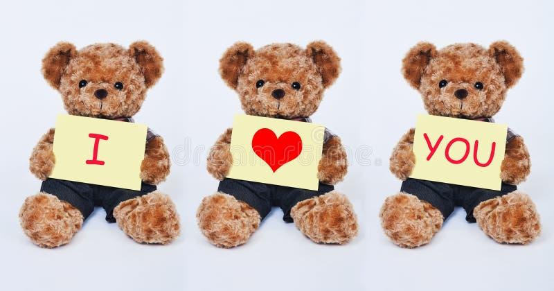 Ours de nounours tenant un signe jaune indiquant je t'aime sur le fond blanc photographie stock libre de droits