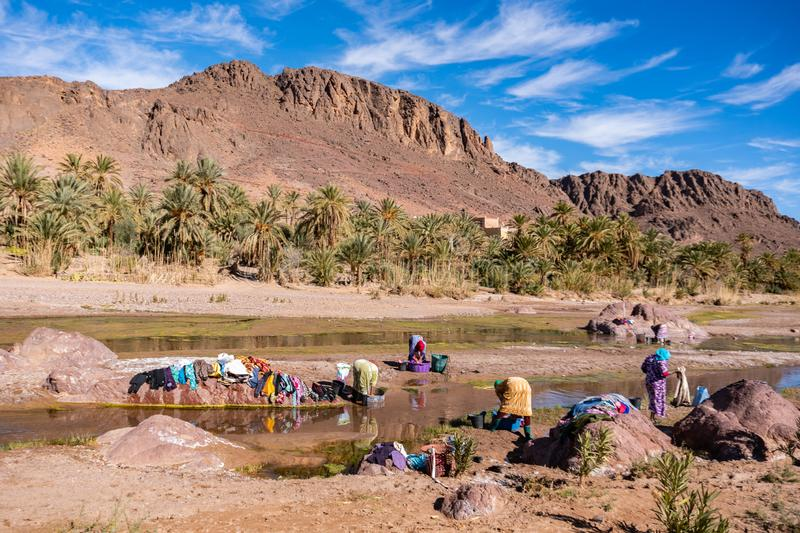 OURZAZATE, MOROCCO - JAN 2019: Berber women wash clothes in the river in beautiful picturesque place Oasis de Fint stock photo