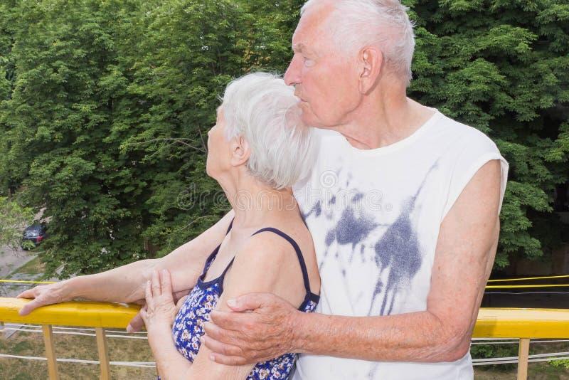 Oustide derecho de los pares mayores en balccony en casa y mirando lejos fotos de archivo