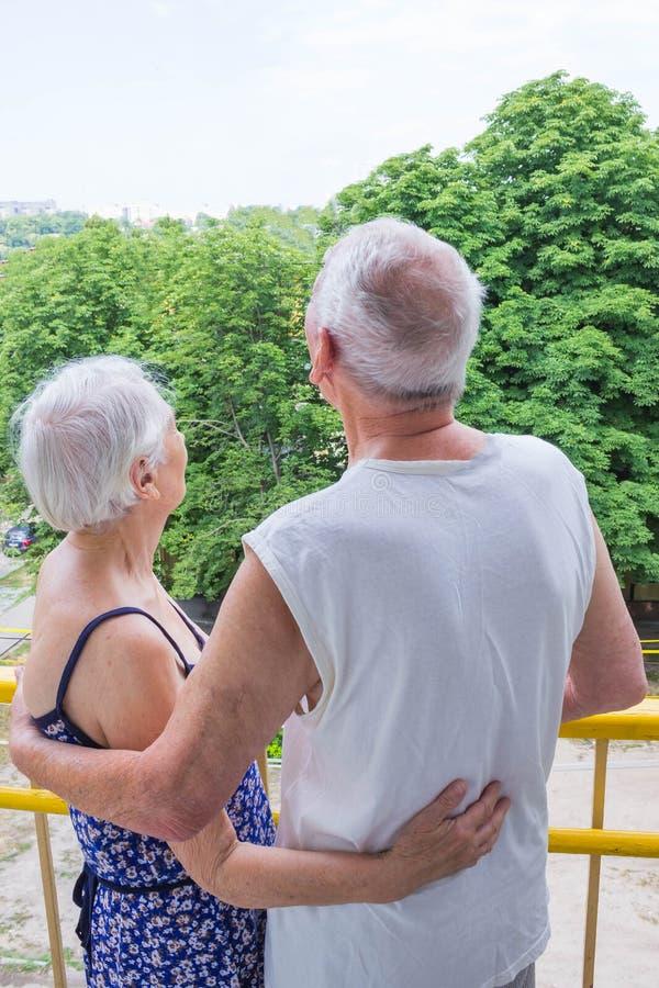 Oustide derecho de los pares mayores en balccony en casa y mirando lejos foto de archivo libre de regalías