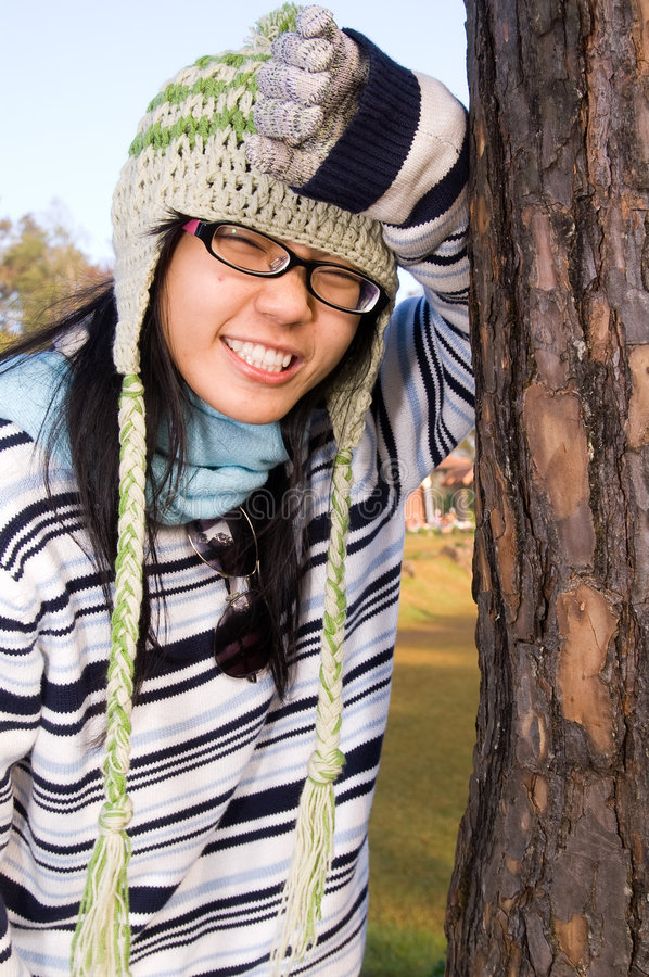 Out in the cold. A girl stands against a tree in the cold air wearing warm clothes royalty free stock image