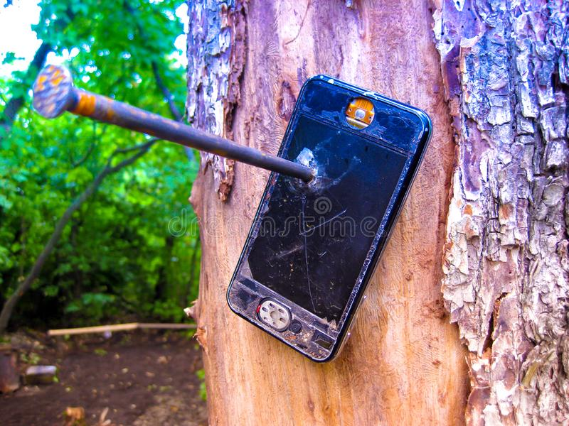 Out of coverage. Nailed to a tree broken phone. stock photos