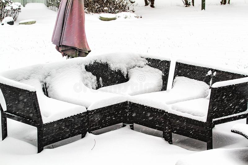 Out door patio furniture in midst of storm covered with snow. Patio and outdoor furniture in the midst of a snowstorm heavily covered in snow in backyard of home royalty free stock image