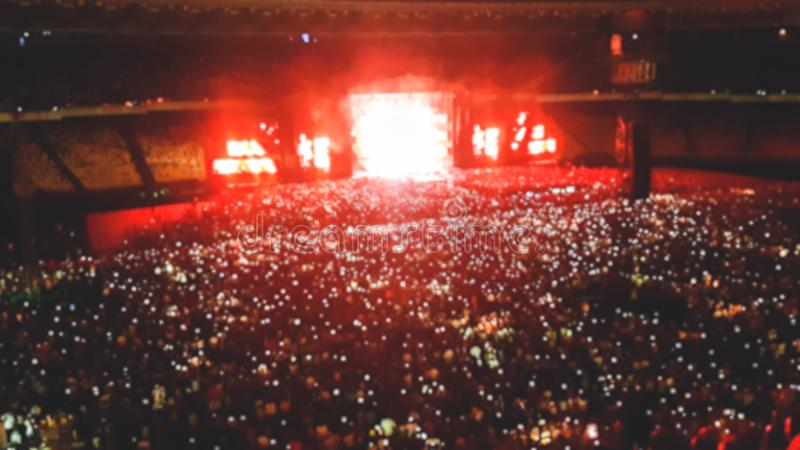 Out of focus image of big crowd of fans sitting on stadium seats watching and listening rock concert at night. Out of focus photo of big crowd of fans sitting stock photos