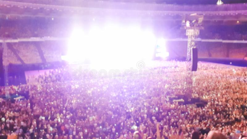 Out of focus image of big crowd of fans sitting on stadium seats watching and listening rock concert at night. Out of focus photo of big crowd of fans sitting royalty free stock image