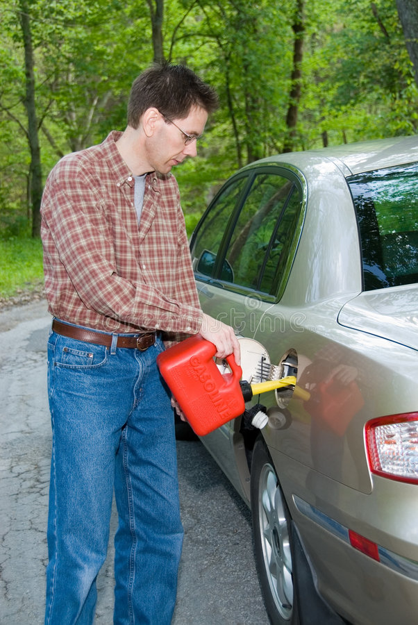 Out of Gas. A man pouring gasoline into the tank of his car from a red gas can while stranded on a wooded country road stock photos