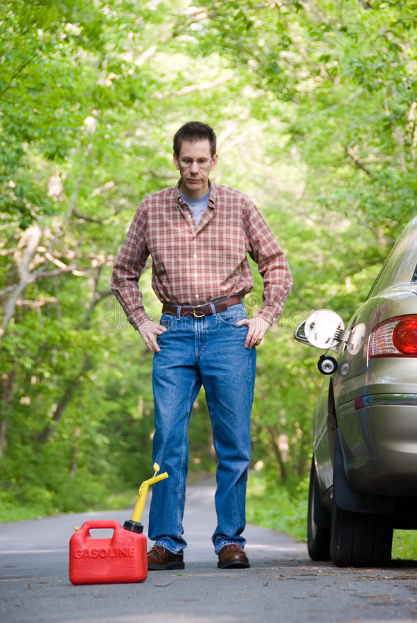Out Of Gas. Upset man on a country road, staring at a gas can sitting on the road next to his car. Focus is on the gas can royalty free stock photo