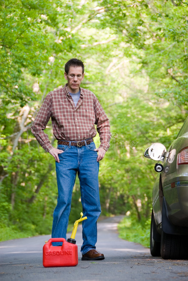 Out of Gas. Upset man on a country road, staring at a gas can sitting on the road next to his car. Focus is on the gas can royalty free stock photography