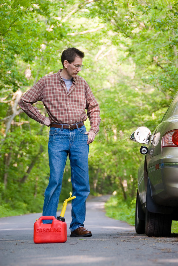 Out of Gas. Upset man on a country road, staring at his car, with a gas can at his feet. Focus is on the gas can stock photo