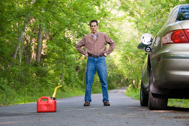 Out of Gas. Upset man on a country road, staring at a gas can sitting on the road next to his car. Focus is on the gas can royalty free stock image
