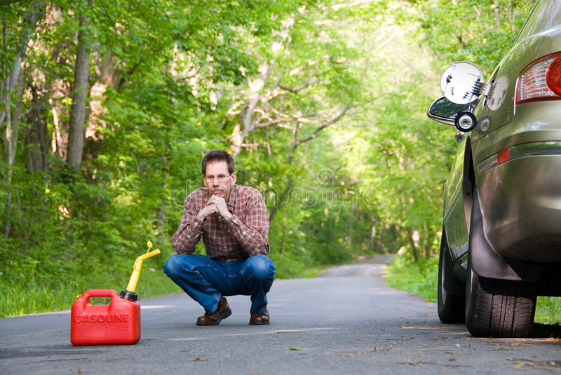 Out of Gas. Upset man on a country road, staring at a gas can sitting on the road next to his car. Focus is on the gas can stock photos