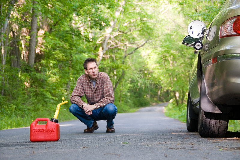 Out of Gas. Upset man on a country road, a gas can sitting on the road next to his car. Focus is on the gas can royalty free stock image