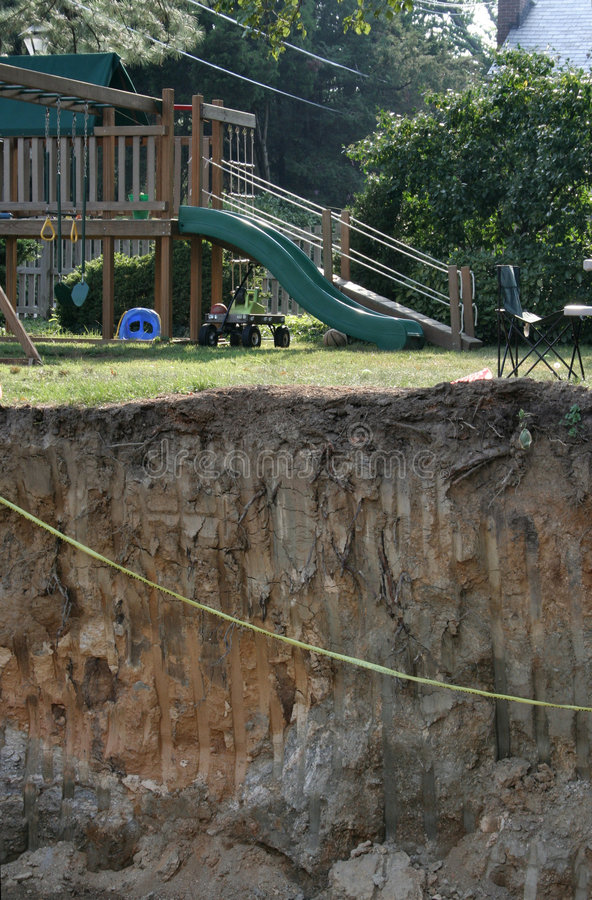 In or out of the Hole. Looking up out of a large construction hole for a basement addition next to a green yard and home playset / swingset. strong & abrupt stock image