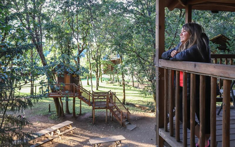 Out'N'About Treehouse Treesort near Cave Junction, Oregon. Cave Junction, Oregon - July 2019:  A woman stands on a platform at the Out`N`About Treehouse royalty free stock photography