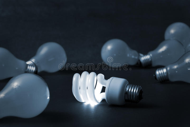 Out With The Old and In With The New. A new energy efficient CFL light bulb shines while the old ones fade into darkness royalty free stock images