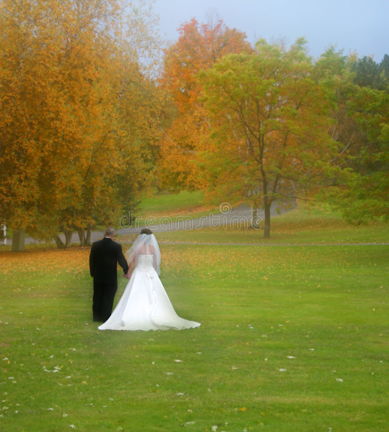 Out standing in the field. Bride and groom with lots of fall colors around them