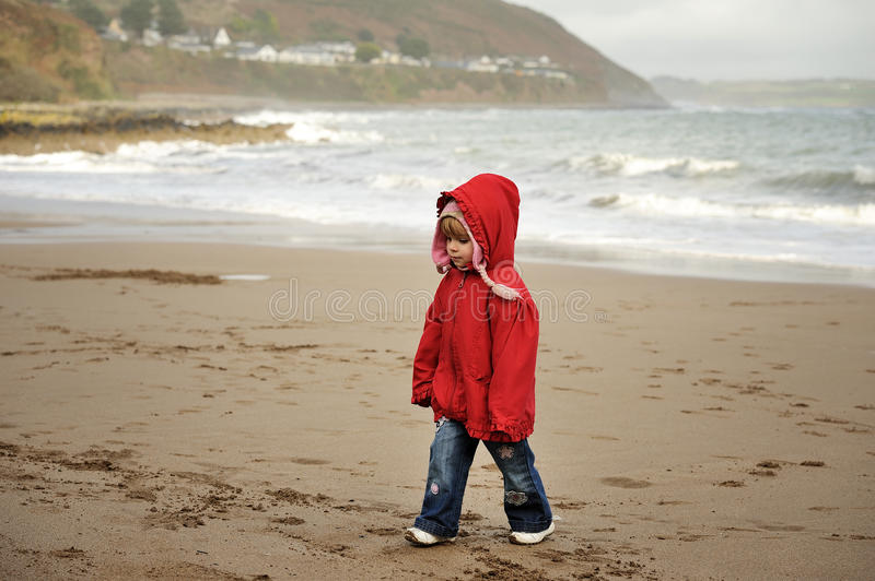 Out for a Stroll. A little girl strolling on a beach royalty free stock image