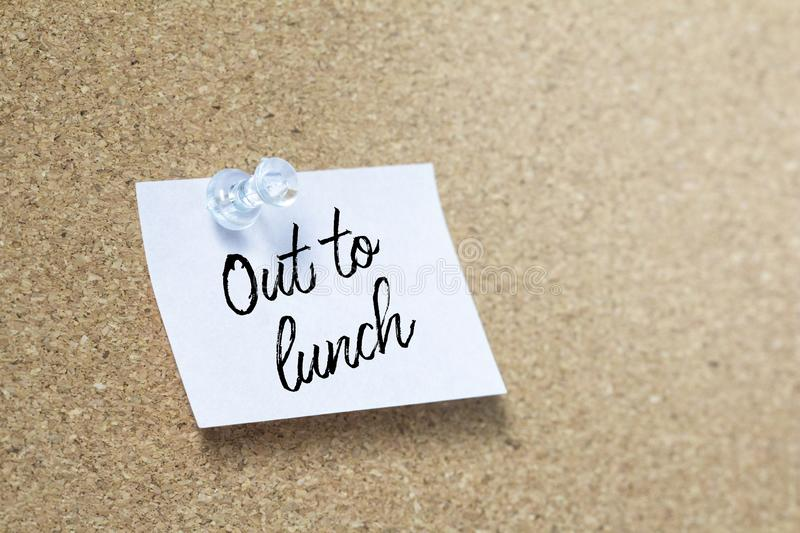 Out to lunch handwriting note on a wooden corkboard royalty free stock photography