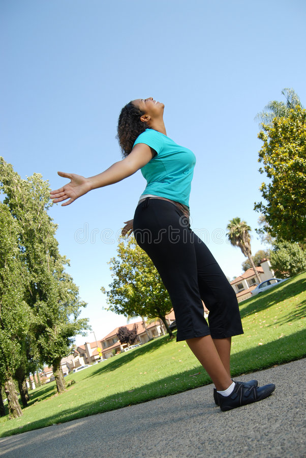 Out on a walk. Happy young woman walking with open arms stock photography