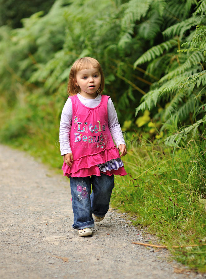 Out for a Walk. A little girl walking on a footpath stock photo