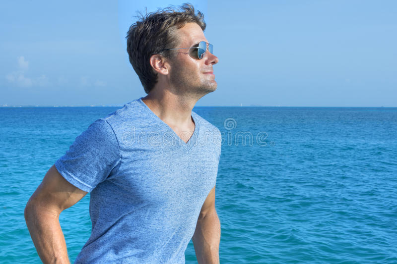 Out on the water. Handsome muscular Caucasian man wearing blue V-neck shirt and reflective sunglasses smiles while gazing out over calm sea under sunny sky royalty free stock photography