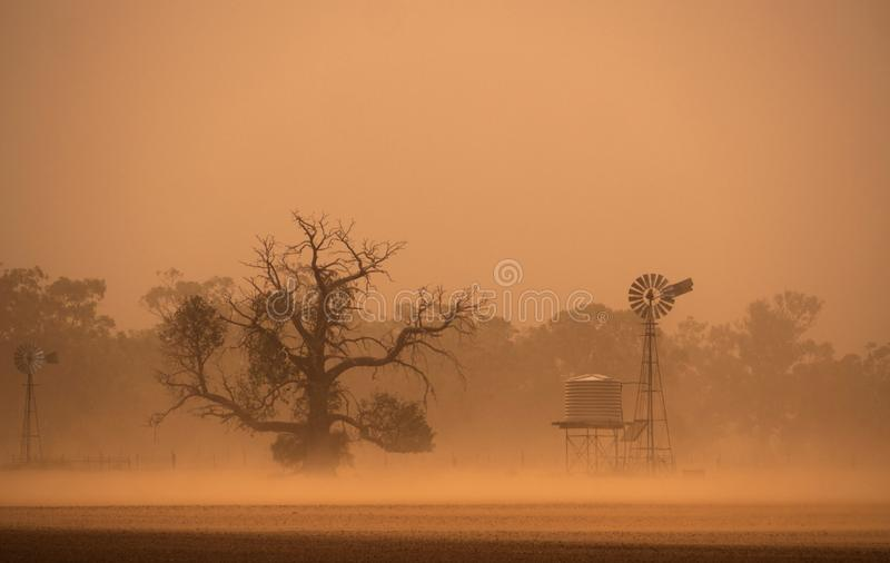 Outback Australia dust storm in New South Wales. Wind pump and water tank in a dust storm driven by strong wind in drought stricken outback Central West New stock photo