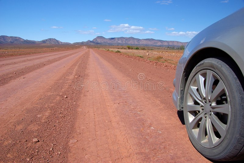 Outback Driving. The front of a silver passenger car driving along a dusty outback road under the hot sun, towards the Flinders Ranges Mountains. Brachina Gorge royalty free stock photo