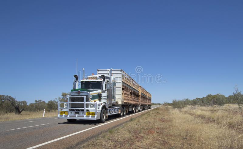 Outback roadtrain with copy space. Road Train cattle truck on an outback Australian highway with blue sky, scrub and copy space stock photography