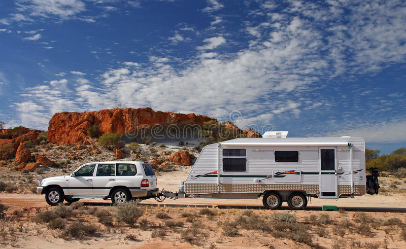 Outback Touring in Australia. Four wheel drive and offroad caravan in outback Australia against a stunning red rock outcrop with an deep blue sky and interesting stock image