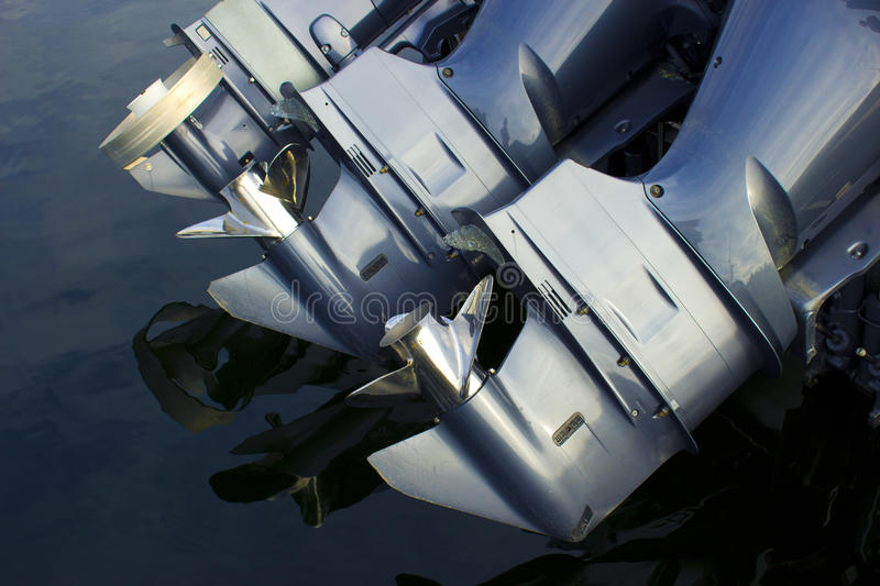 Outboard Boat Engines. Three outboard boat motors over water royalty free stock image