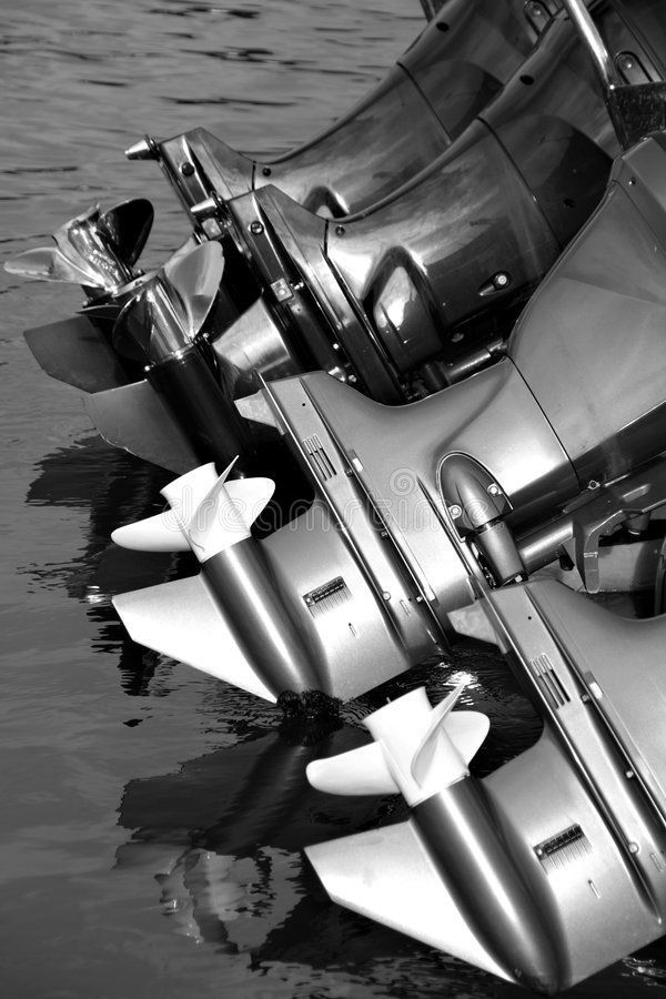 Outboard engines. Tilted Outboard engines at rest in a harbour suggesting power stock photography