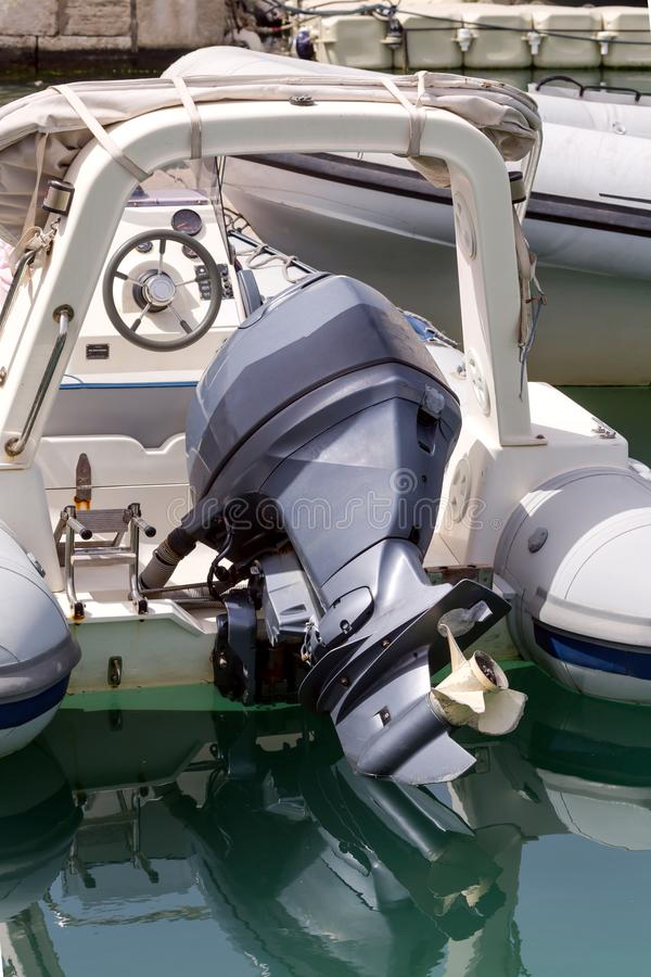 The outboard motor. The black, used, outboard motor on a moored boat close-up stock images