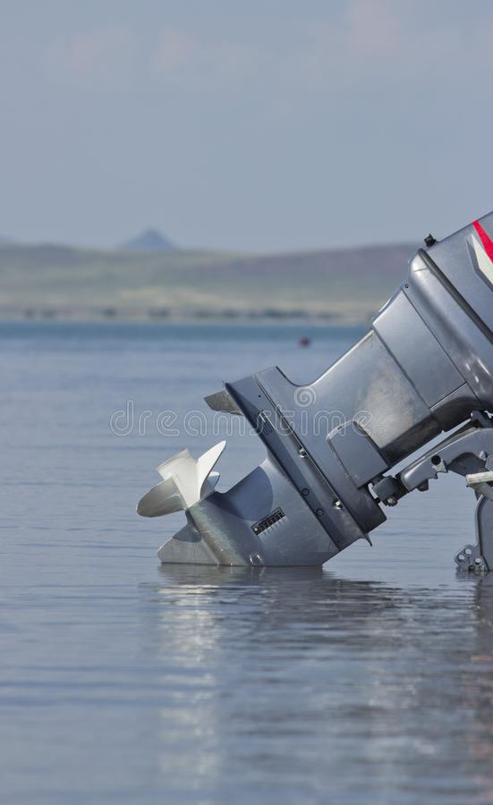Outboard motor lowered into the water. A boat engine is waiting to be started royalty free stock images