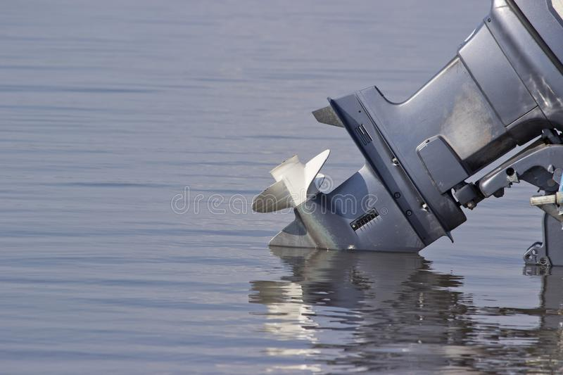 Outboard motor lowered into the water. A boat engine is waiting to be started stock photography