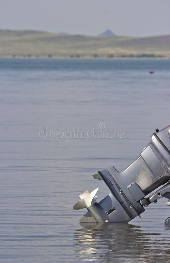 Outboard motor lowered into the water. A boat engine is waiting to be started royalty free stock photo