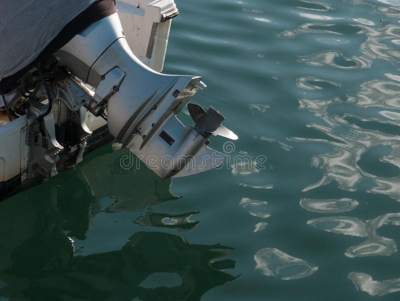 Outboard motor with propellor out of water, on the back of a small boat. Or fishing vessel royalty free stock photos