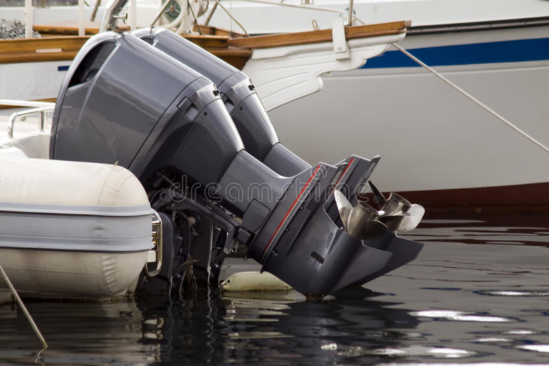 Outboard motorboat engines. Twin black outboard motor engines on a boat stock images