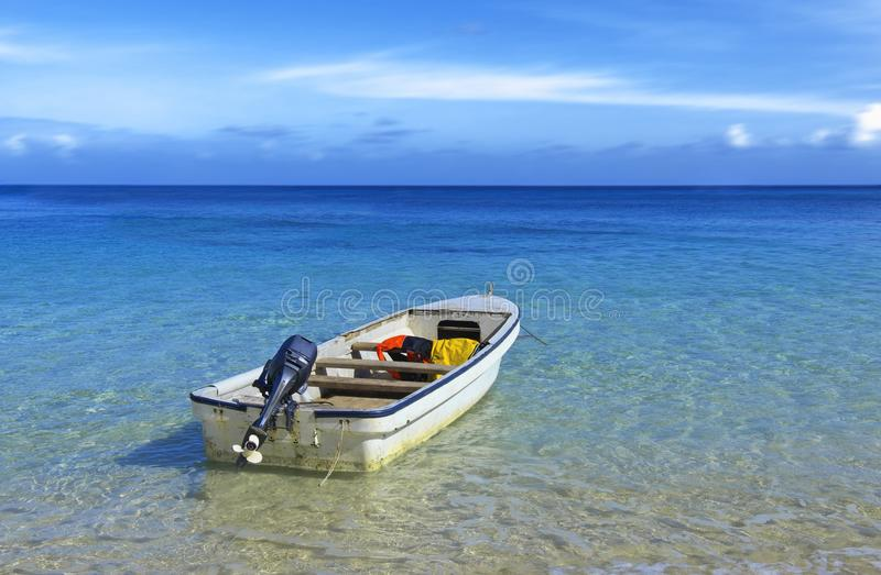 Outboard motorboat on tropical waters. Old white outboard motorboat moored in shallow clear water on blue tropical sea stock photos