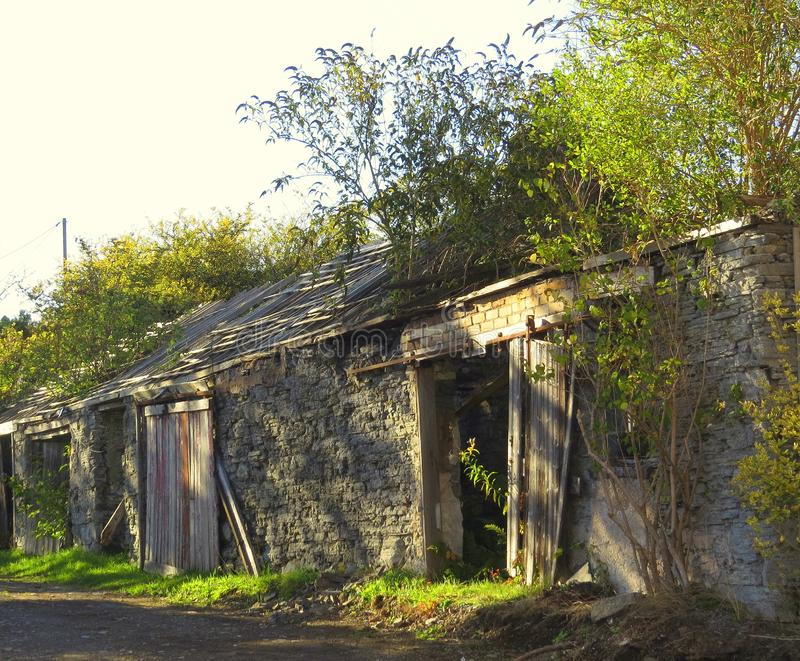 Outbuildings, derelict, neglected, ruins. A row of outbuildings, with ruined slate roofs, wooden sliding doors off the rails, rough grass verge stock photo