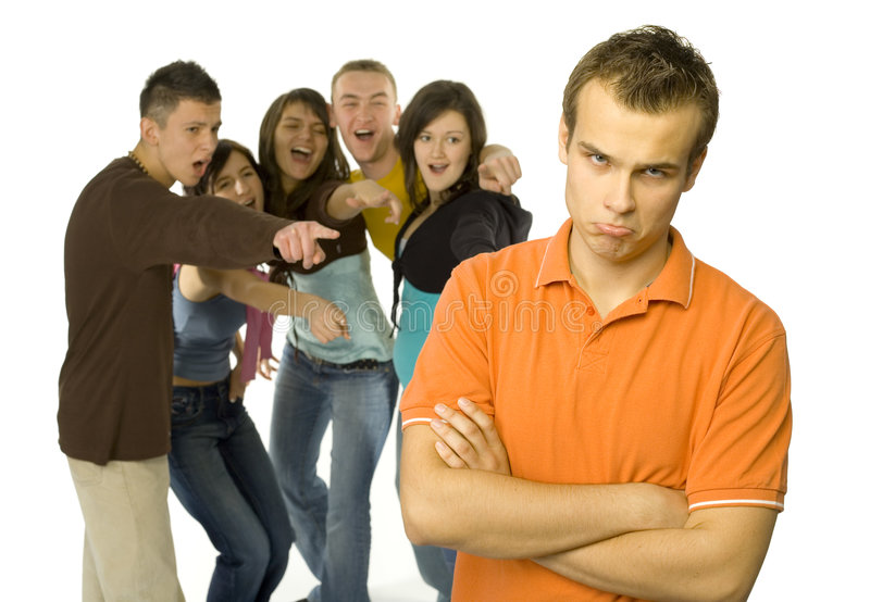 Outcast. Sad boy is standing in the foreground. There're group of mocking teenagers behind him royalty free stock photo