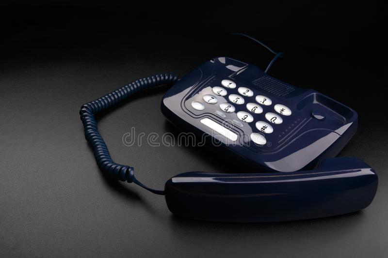 Outdated push-button telephone with handset on black background stock images