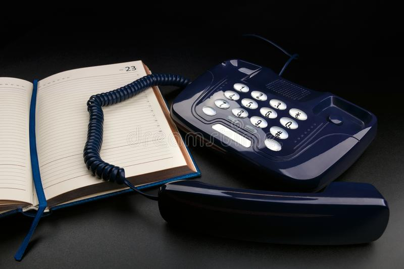 Outdated push-button telephone with handset and personal organizer on black background stock image