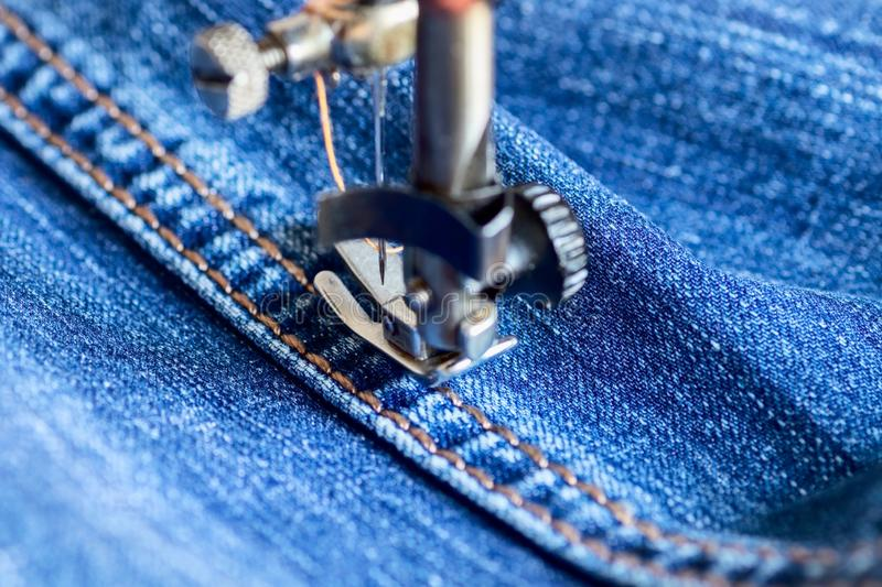 On an outdated sewing machine with a mechanical manual drive, men`s pants are made of a dense blue denim material. Close up stock photo